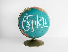 12 Vintage Globe with gold base and arm. Painted with Explore in white. 12 wide x 15 high 8 wide base This is a brightly-colored