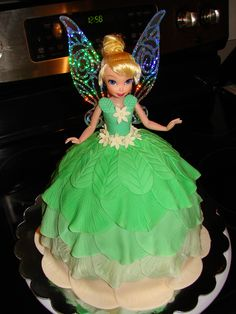 not a fondant fan but so pretty  Tinkerbell Doll Cake - Tinkerbell doll cake for a little girl turning two at a local homeless shelter.  The doll is a toy for her to keep when the cake is gone.  The wings are part of the toy, and added a lovely effect, I think.  Chocolate fudge cake with buttercream frosting.  Thanks for looking!