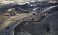 Heavy earth moving machinery move raw tars sands at the Syncrude tar sands mining operations near Fort McMurray, Alberta.