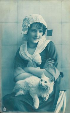seated Dutch girl facing front with arms folded looking half right, white cat lying on her lap looking up/left