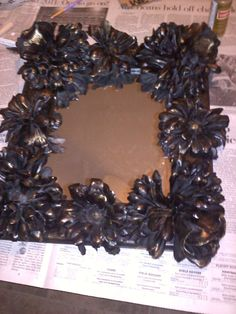 This is a mirror I made for one of my sisters for Christmas. I dipped fake flowers I plaster of paris and glued them on an unfinished frame. I spray painted it all black then dry brushed gold over the flowers. :-):
