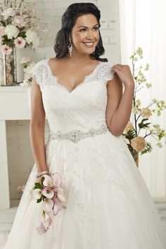 1500 Unforgettable (Plus Size) by Bonny Bridal -Soft lace creates a feminine cap sleeved bodice slowly cascades down the back of the cathedral train. The romantic eyelash lace accentuate the vintage neckline. *Close up picture is shown with belt style 9501 (sold separately)