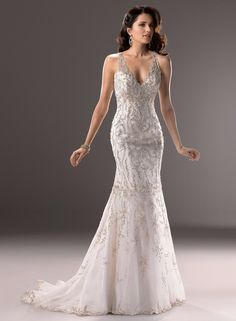 The lavish embroidery and sparkling beads of this fit and flare gown capture the dramatic flair of a bygone era. Finished with scalloped illusion neckline, and button over zipper back closure Size 10