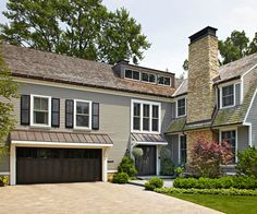 The right touches can give a home's facade a charming character boost. A short, sloping roof over the garage that matches the roofline above the front entry streamlined the exterior of this Dutch Colonial house and made room for a grand new master suite. Colonial Style Homes, Dutch Colonial, Style At Home, Black Garage Doors, Front Doors, Entry Way Design, House Front, Front Porch, Porch Roof