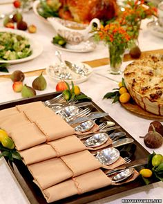 How to fold a napkin for buffet use. Martha Stewart.  I love the feel and decor of the whole table, horizontal runners as placemats, the adorable little fruits, the colors and that pretty tray with the folded napkins ;) very doable for anybody and inexpensive. mtdb.