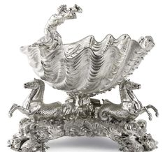 John Bridge (Dorset 1755 - London 1834). A George IV silver Dessert Bowl Centrepiece, London 1824. The large clam shell with a surmount of a twin tailed triton blowing a conch, the shell supported by three hippocamps in a wild sea setting and supported by three groups of clam shells, coral and turtles. A similar set of four silver-gilt dessert bowls with covers were made for the Royal Collection by John Bridge 1826-27.Provenance:Sotheby's, New York, 14th April 1999, lot…