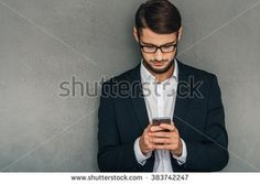 Business message. Confident young man in glasses using his smartphone while standing against grey background - stock photo
