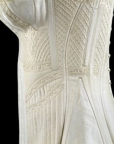 1825-1835 ca. Corset, England White cotton corset with silk trapunto work. Busk down centre middle, separate breast double-gussets with trapunto strap in centre of each breast. Corded and quilted work down sides of corset, armholes set quite far back, and laces down the back. collections.vam.ac.uk