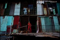 Photo of the Day: Colorfully Decrepit in Bangladesh | Residents of a slum apartment complex stand watchful in Dhaka, #Bangladesh on August 25, 2012. (Zoriah/Flickr)