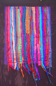 """Photographer quote: """"One of the most memorable parts of my trip to Gambia was the traditional markets which were an overwhelming rush of colour, people, sounds and smells. The brights colours and texture of these textile pieces are inspired by the lively and vibrant markets.This textile piece is made with strips of recycled sari silk and embroidered with segue ribbon."""""""