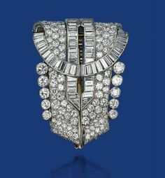 AN ART DECO DIAMOND BROOCH, BY OSTERTAG Of stylized shield outline, with two pavé-set diamond scrolls enhanced by baguette-cut diamond lines and circular-cut diamond collets to the side, 1930s, 5.5 cm, with French assay mark for gold