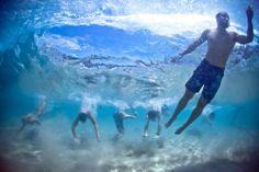 People Swimming under crashing waves