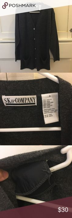 """SK & Company Vintage Partial Wool Cardigan L This sweater is so vintage it has shoulder pads! Of course, those are easy enough to remove. It is charcoal grey and in excellent condition! It is Ribbed on the bottom and the sleeves. It has all its buttons and two pockets on the front. It's sized as a small, but the flat measurements are 21"""" chest, 19"""" at the bottom, 31"""" length--and the great thing about a Cardigan is you can wear it open, so you can take all the inches you need! SK & Company…"""