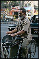 Man sharpening knifes on the street, Colaba. Mumbai, Maharashtra, India (color)