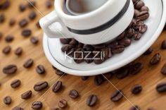 cropped image of coffee cup and coffee beans. - Close-up cropped image of coffee beans and black coffee cup on wooden table.