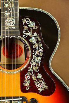 Here we have one of the most beautiful guitars you will ever see! A Gibson SJ-200 Masterpiece Custom acoustic guitar.This is definitely not your typical SJ-200. The inlay work of pearl and abalone is very ornate. These are not your typical inlays. These are some of the finest you will see on a gu... #beautifulguitars