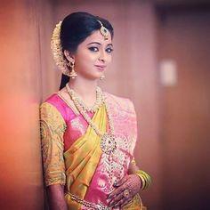 South Indian bride. Gold Indian bridal jewelry.Temple jewelry. Jhumkis.Yellow and pink silk kanchipuram sari.Braid with fresh flowers. Tamil bride. Telugu bride. Kannada bride. Hindu bride. Malayalee bride.Kerala bride.South Indian wedding.
