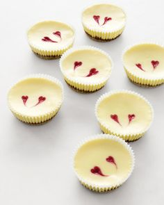 Cheesecakes with Raspberry Hearts #recipe --   What's better than digging into a slice of cheesecake? That's easy -- eating the whole thing! Give each guest a tiny version of the classic creamy, graham cracker-crusted treat. These cakes manage to trump the original, thanks to whimsical hearts made from raspberry puree.