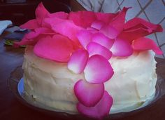 Chocolate layered birthday cake with white icing and pink rose petals