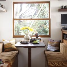 This breakfast nook takes advantage of the outdoor view and brings it in, with elements like the raw-edge table, wood shelving and neutral tones. Yellow flowers in a clay jar. Decor, Dining Nook, Interior, Home Decor, Room Inspiration, House Interior, Dining Room Inspiration, Modern Kitchen Design, Small Dining