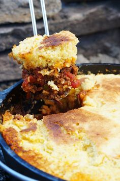 Dutch Oven Camp Chili & Cornbread _ Nothing is more satisfying than coming back to a big camp fire after a long day of hiking & making a hearty meal! The spicy & smokey chili soaks into the bottom of the sweet cornbread!