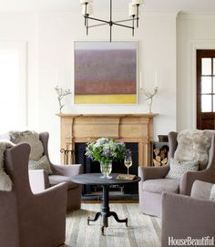 Four swivel chairs from Lee Industries — slipcovered in a Covington Fabric & Design linen and topped with sheepskin pelts — offer a cozy gathering place in the family room. Antler candelabras from At Home in the Country flank a painting by Karen LeSage. Bryant chandelier by Thomas O'Brien for Visual Comfort. Pottery Barn rug.