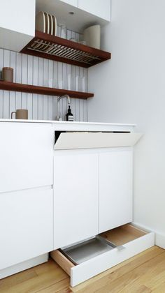 """The cabinet fronts are flat MDF panels with a sprayed, white lacquer finish. The toe kick drawers have stainless steel edge pulls (""""because they are basically invisible""""), and the cabinets have recessed bevels that serve as pulls. Kitchen Cabinets Measurements, Installing Kitchen Cabinets, New Kitchen Cabinets, Kitchen Drawers, Kitchen Storage, Kitchen Decor, Upper Cabinets, Kitchen Mats, Studio Kitchen"""