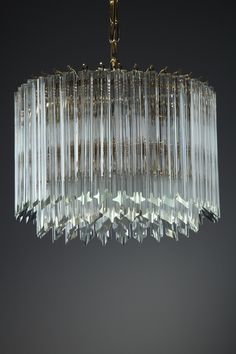 Circular chandelier designed by Paolo Venini for Murano in the 1970s, with long glass crystals on gilded metal mounts. It has 4 light bulbs. Good vintage condition. Complete.