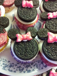 Minnie Mouse Cupcakes. Use half a tooth pick per mini oreo to keep the ears on. Use Duff pink fondant for the bows! Easy peasy