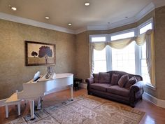 Piano room with wood floor, crown molding, recessed lights and bay window. Could also be used as a formal living room.