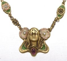 The following three lots built by Steve Schall, New York goldsmith, creator of jewelry in the Art Nouveau style. 18K yellow gold necklace of shaded and plique a jour enamel, diamonds and an amethyst: sculpted woman with flowing hair ornamented by diamond-set enameled poppies, an amethyst cobochon and green plique a jour suspends from a link chain composed of alternating roquille and diamond-set enameled panels.