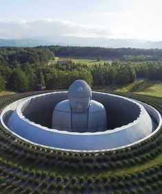 tadao ando surrounds giant buddha statue at a japanese cemetery with landscaped hill
