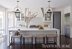 With a pair of outdoor ceiling lanterns from Lantern & Scroll and two pairs of Hickory Chair stools, symmetry is the order of the day in this farmhouse kitchen. - Photo: Paige Rumore / Design: Rachel Halvorson