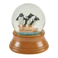 This charming 35mm snow globe features a trio of realistic-looking penguins gathered together on an icy perch. Do these penguins and yourself a favor and turn or shake the globe to create a glittery s