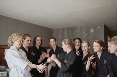 Bride and her bridesmaids in matching robes as they get ready for the wedding. Downtown Detroit Outdoor Rattlesnake Club Wedding on the Detroit Riverwalk in Detroit, Michigan by top rated Detroit wedding photographer, Kari Dawson