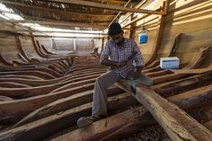 Laborers chisel and shape timber hull ribs during handmade construction of an ancient timber dhow. Sur, Ash Sharqiyah Region, Gulf of Oman, Sultanate of Oman.