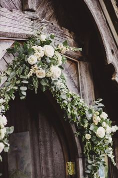 Boutique Blooms: Boutique Blooms Floral Design & Styling. Dusky pink, peach and white spring flowers adorned the silver/grey foliage archway of the ceremony church in Surrey Photo credit: Lola Rose Photography