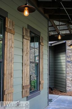 Front Porch Details Custom-built lakehouse features exterior details including natural stained shutters, industrial-style lighting and exposed rafters under a tin roof. Image Size: 667 x. House Paint Exterior, Exterior House Colors, Siding Colors For Houses, Craftsman Exterior, Green Siding, Wood Shutters, Houses With Shutters, Window Shutters Exterior, Farmhouse Shutters