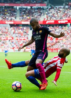 Rafinha of FC Barcelona duels for the ball with Alberto Lora of Real Sporting de Gijon during the La Liga match between Real Sporting de Gijon and FC...