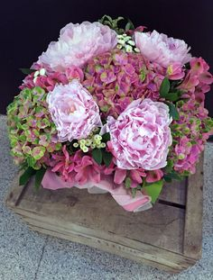 Centro con flores en tonos rosa y verde.