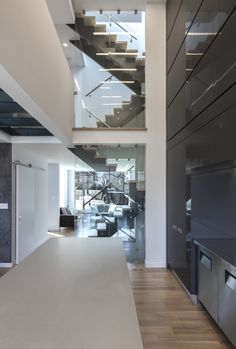 rzlbd > Instar House > kitchen & central staircase > The staircase / void which sits on the centre of the larger volume, not only allows for visual communication, also divides each floor level into two section.