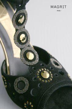 Magrit. Materiales y adornos. ANTE y PIEDRAS:  Elegante calado fabricado en suave ante negro con un T-bar adornado con unos círculos repletos de brillantes piedras en colores negro, dorado y cristal, que bajan hasta la pala. SWAROVSKI ELEMENTS --------------Materials and ornaments. SUEDE & STONES:  Elegant lace made of soft black suede with a T-bar adorned with circles full of shiny stones in black, gold and crystal, up to the vamp. SWAROVSKI ELEMENTS