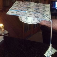 Graduation hat made with money. Use poster board as your template and tape 8 bills across the top and 4 bills around for the headband. Fan fold 2 bills as a tassel and attach with ribbon and a coin in the center for a button. Add your sentiments and Class of 20.. on the inside and don;t forget to use the graduates school colors.