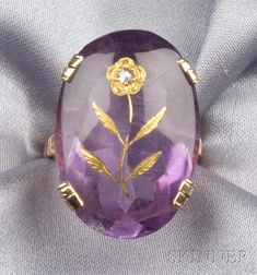 Antique 14kt Gold, Amethyst, and Diamond Ring,  the mixed-cut oval amethyst inlaid with a gold and rose-cut diamond flower, foliate and black enamel shoulders.