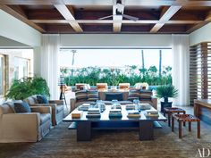 In George Clooney's Mexican home by Legoretta + Legoretta, the living room features a slipcovered sofa and armchairs and a pair of stools by Casamidy grouped around a cocktail table by SL Westwood Design.