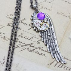 """I want one of these so badly! Steampunk Necklace Wing Steam Punk Jewelry - Silver Wing Purple Helitrope - Vintage Watch Movement- 24"""" Black Chain Gunmetal. $39.00, via Etsy."""