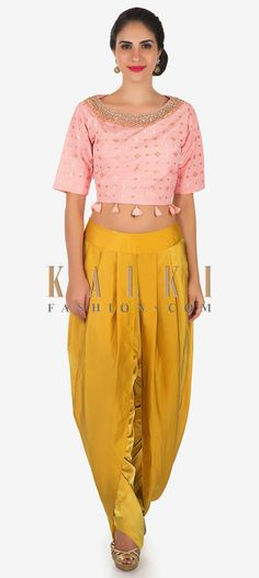 Buy Online from the link below. We ship worldwide Click Anywhere to Tag Pink crop top and yellow dhoti suit in moti sequin work only on Kalki The pink top is featured in silk fabric whereas the dhoti pants comes in satin. The pink top is embellished in moti and sequin work with attached tassels at waist line. The yellow dhoti pant in satin will make a standout addition at every party you go. Slight variation in color is possible.