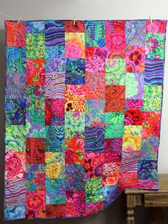 This vibrant lap quilt is completed and ready to ship to you! It is made using a bright, cheerful Kaffe Fassett fabrics, mostly beautiful florals. It is bold, colorful, and truly one of a kind! It is quilted in raspberry pink thread in a meandering wavy pattern. The binding is made from one of my favorites fabrics and is machine stitched to both sides for durability . The batting in the middle of the quilt is 100% cotton that is thin and lightweight, but also warm. This quilt is backed in a…