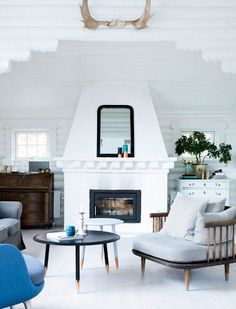 A Danish living room featured in Femina boasts the Scandinavian winter must-have: a wood-burning fireplace, as well as plenty of locally made ceramics and furniture. Eight layers of white paint brighten up the log cabin-like interior. (Seriously check out the rest of the tour; it's straight out of the movie Elf.)
