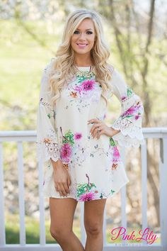 You'll be wishing your toes were in the sand, watching the sunset in this beautiful floral dress! Featuring a beautiful floral fabric with green, light blue, fuchsia, yellow, and white fabric on ivory fabric, it simply shines!